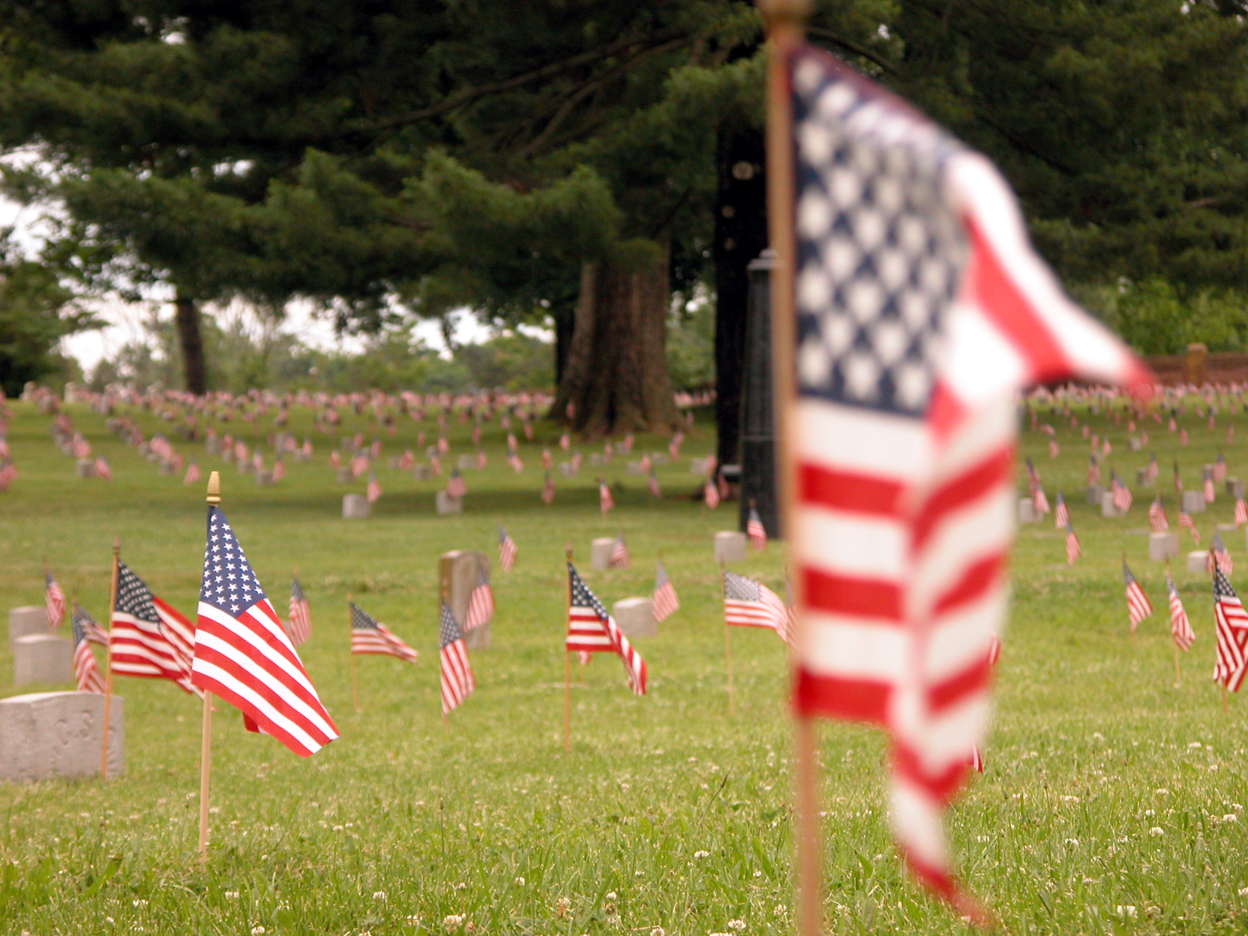 American flag waving in wind in foreground with soldier graves decorated by American flags in background