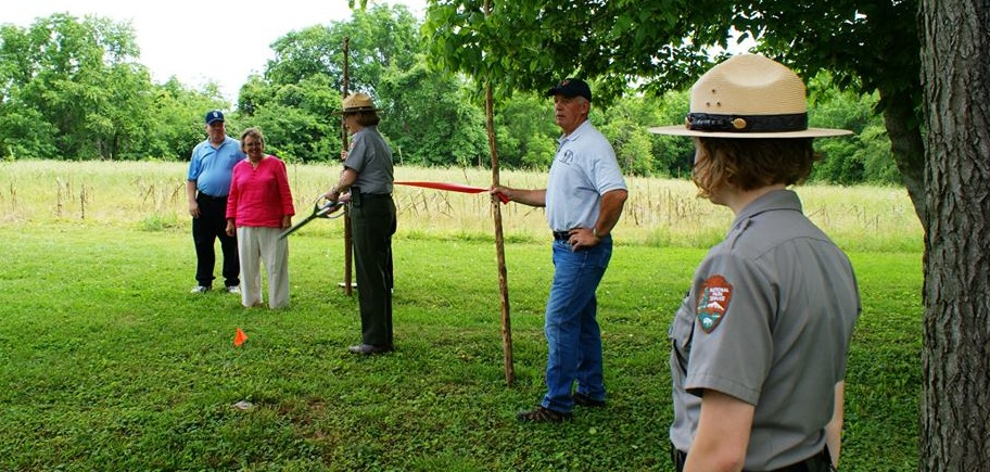 Two park employees and three Friends of Wilderness Battlefield members dedicate new trail by cutting red ribbon with large scissors