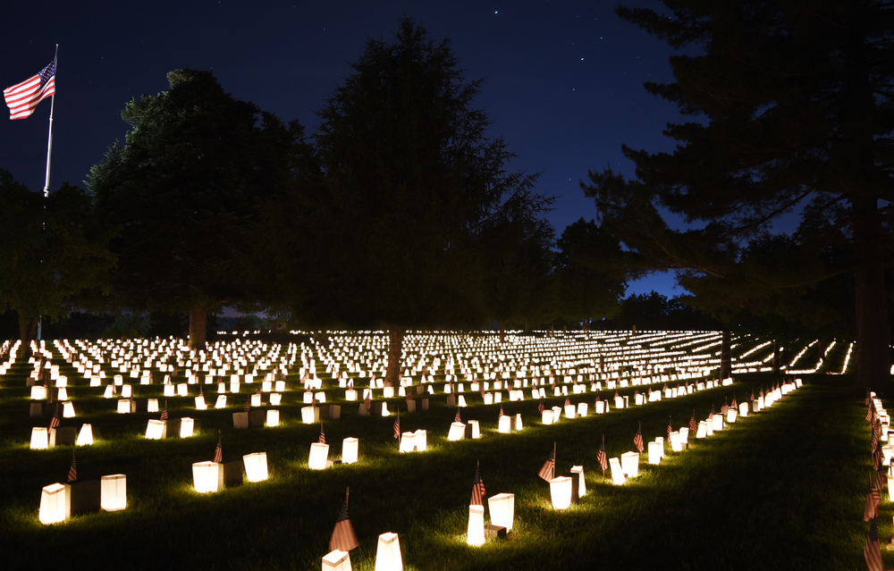 Photo taken of the Fredericksburg National Cemetery at night with small luminaries on each grave and the U.S. flag in the background