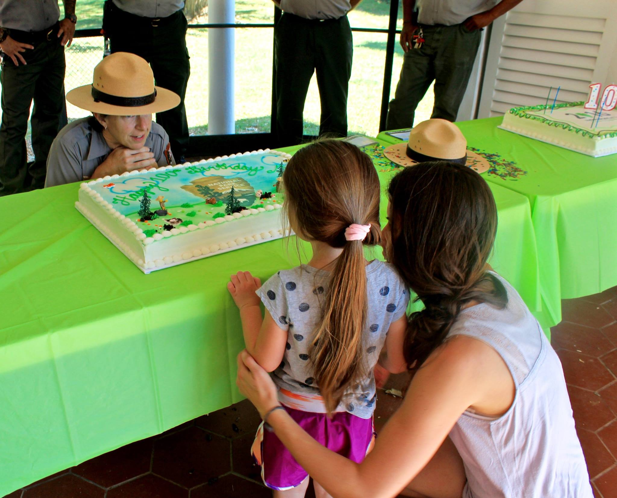 Park ranger with flat hat kneels behind table with cake to talk to small child and her mother
