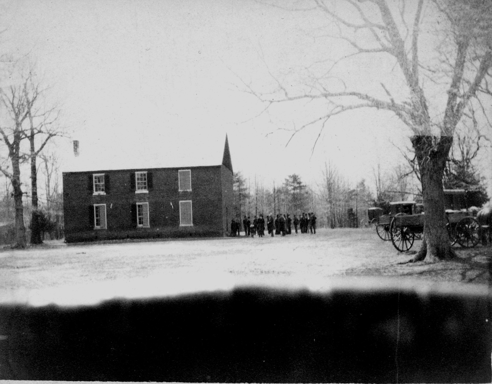 Black and white photo of veterans gathering to the right of a two-story, rectangular, brick building.