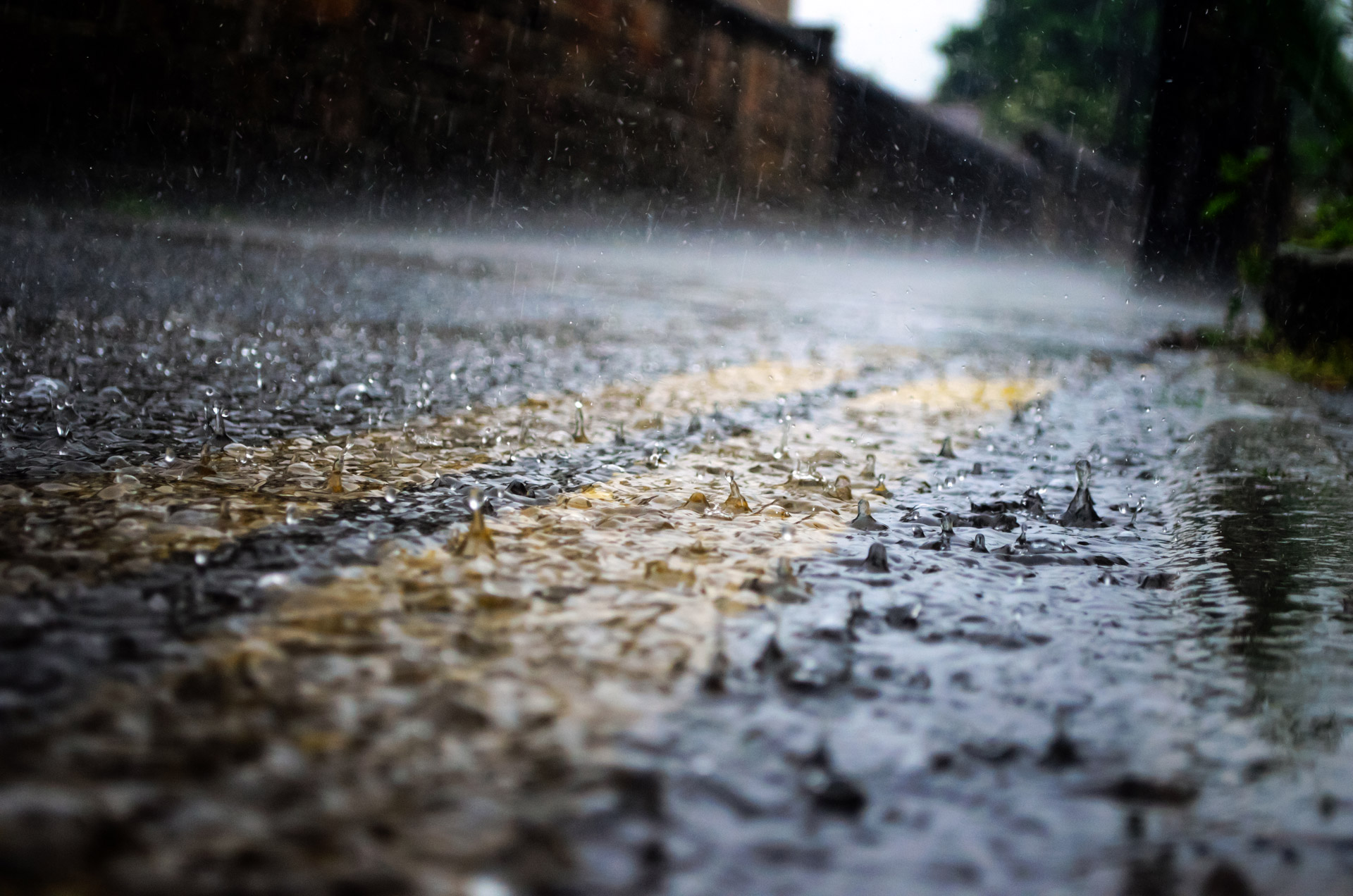 Close-up of road pavement with rain drops falling rapidly