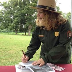 Park employee signing book on grounds of Ellwood