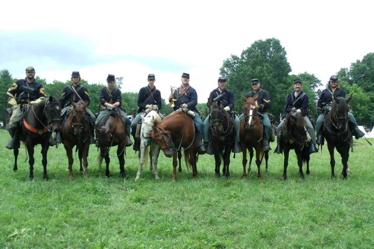 Line of living historians representing members of the cavalry on horseback