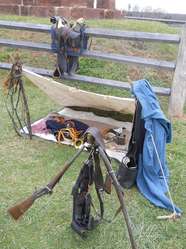 Display of arms stacked, including saddle on fence and tent with camp implements