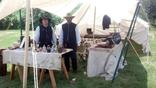 Hospital tent filled with three tables and medical equipmentwith two reenactors standing facing the camera