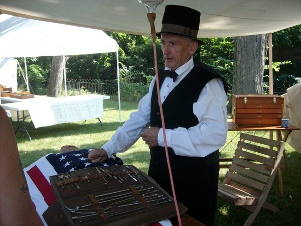 Man in white shirt with black vest and top hat stands in tent with embalming kit