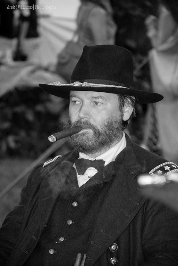 Reenactor dressed in Union general's uniform with hat smoking a cigar