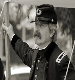 Man in general's uniform and hat leaning against pole of tent