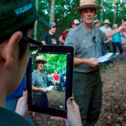 Intern holds iPad to livestream as park ranger gives program