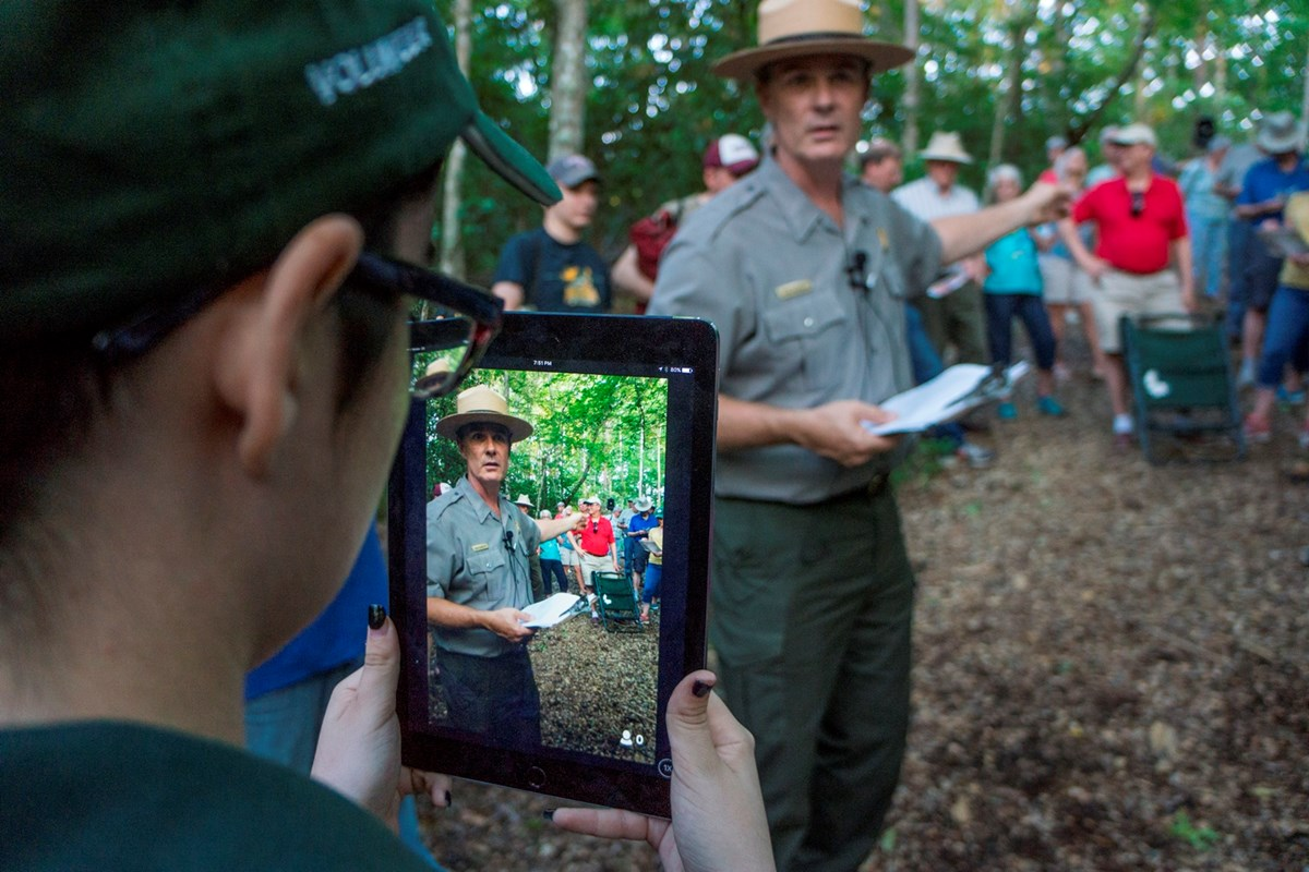 Intern holds iPad as park ranger giving program appears on screen