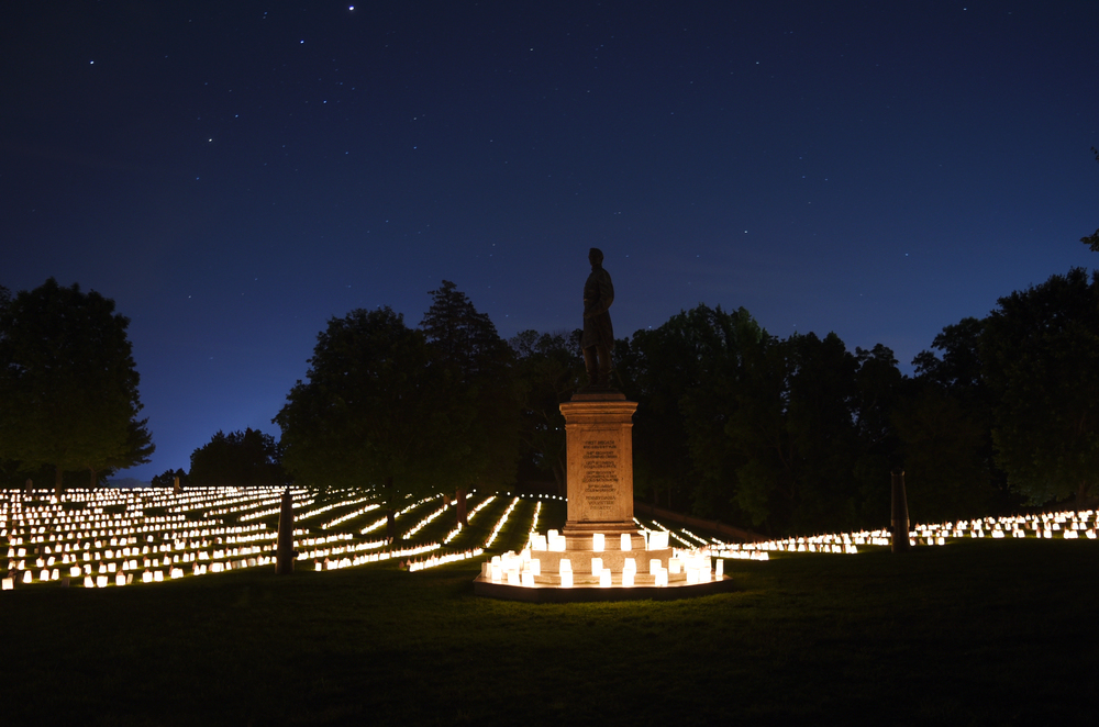 Graves illuminated by candles with large monument in center at night