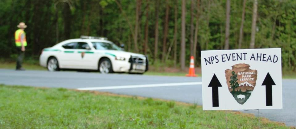 "Sign with arrowhead and arrows reading ""NPS Event Ahead"" with law enforcement ranger and park car in background"