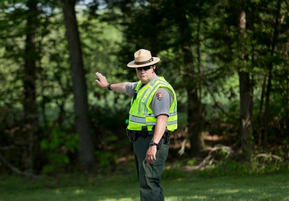 Law enforcement park ranger in yellow vest directs traffic