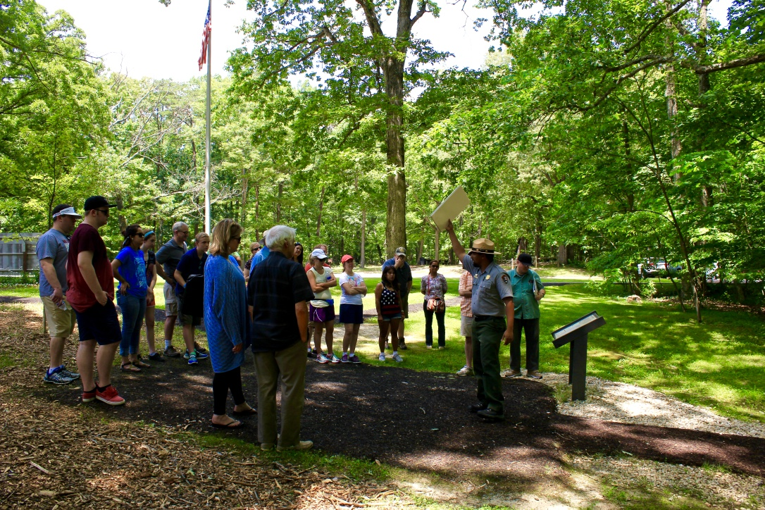 Ranger leads group of visitors on guided walking tour with trees and flag pole in background