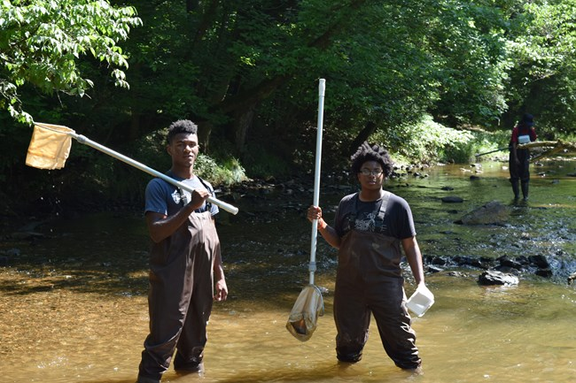 Two people pose for a photo while collect macroinvertebrates