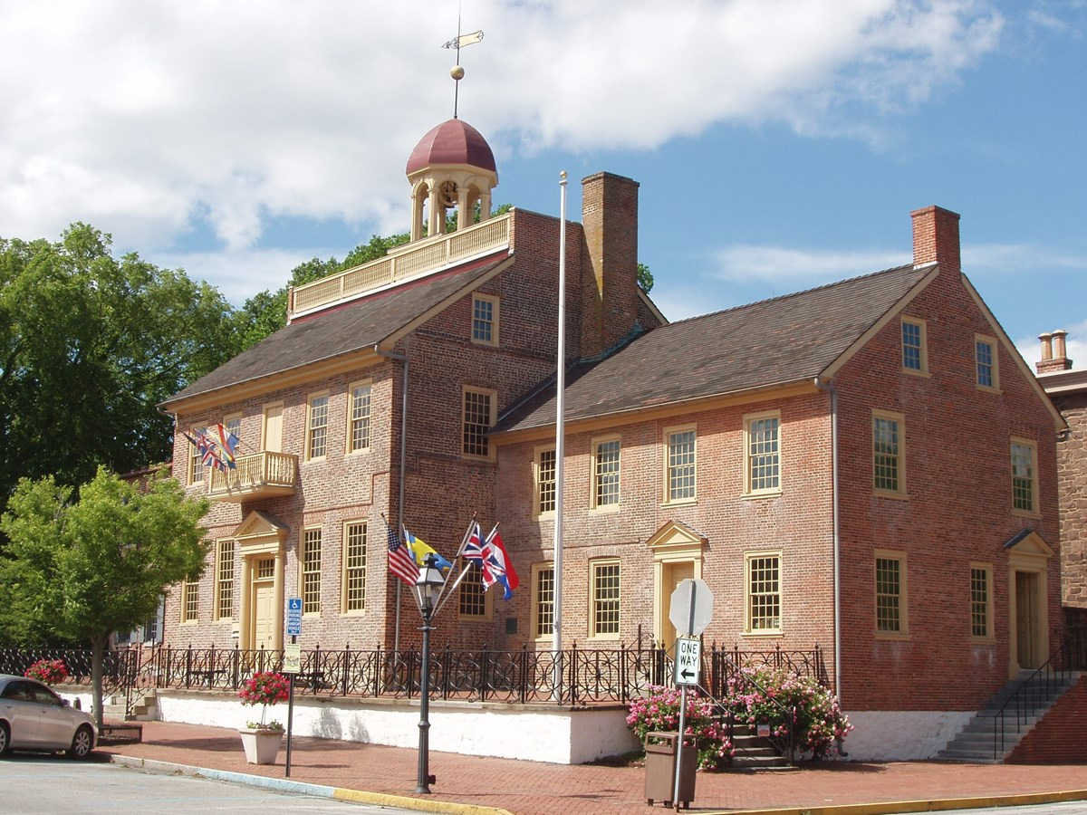 The front and right side of the New Castle Court House are shown on a bright sunny day.