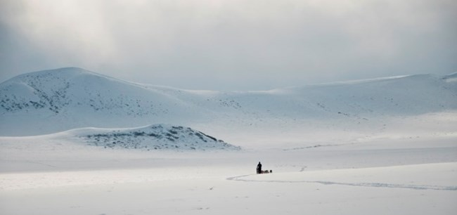 A musher in a distant and vast snowy tundra landscape with mountains and sunlight shining down into the valley in the distance