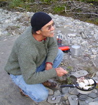 Sculptor Hugh McPeak cooks his dinner while on the 2005 Artist in Residence Patrol.