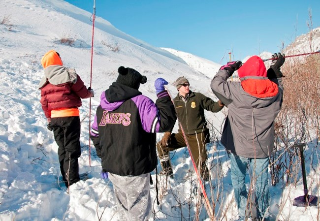A ranger and students conduct an activity outdoors in winter