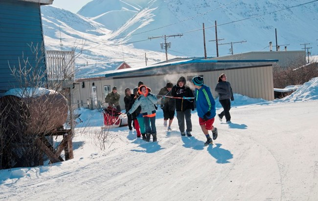 Anaktuvuk Pass kids pull a dogsled on the snowy roads through town