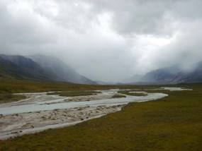 Noatak river winding through a broad valley on a cloudy day.