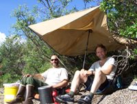 Resident Artist Mark Ross and Ranger Pete Christian get out of the sun under a tarp.