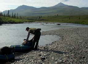 Ranger preparing inflatable boat for days float on the Tinyaguk River