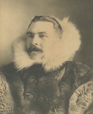 Historic photo of Gordon Bettles wearing an elaborate fur coat with an oversized ruff.