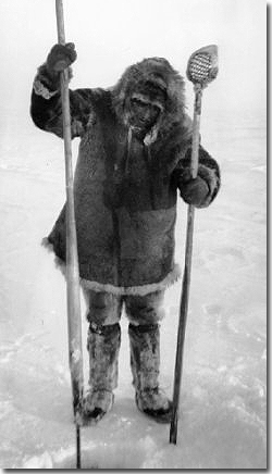 Coastal Eskimo ice fisherman wearing caribou skin parka, pants, and boots