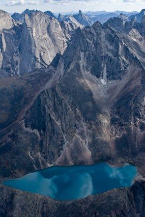 The grey granite spires of the Arrigetch Peaks frame a turquoise blue cirque lake.