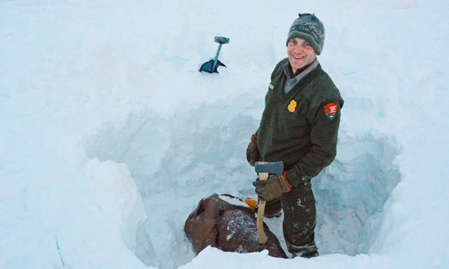 Gates of the Arctic Ranger stands smiling in a deep pit dug to extract an old barrel from the wilderness