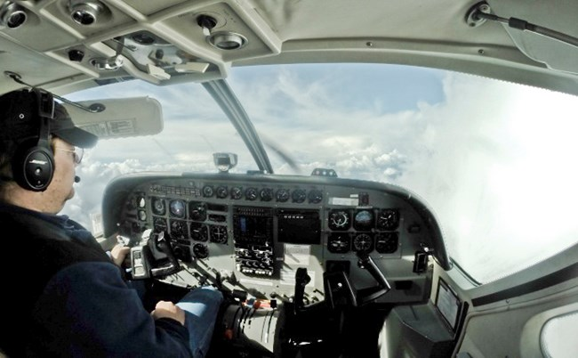 The inside of an airplane cockpit, looking out at the clouds