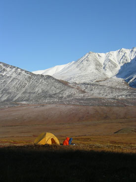 Image of two wilderness travelers sitting on the tundra outside their tent.