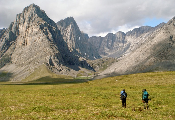 Two backpackers approach the majestic Hidden Valley in the Arrigetch Peaks area of the Brooks Range