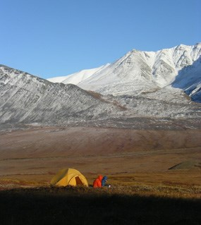A tent and two campers on a sunny and cold day with a snowy mountain in the distance.