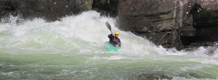 kayaker running the rapids