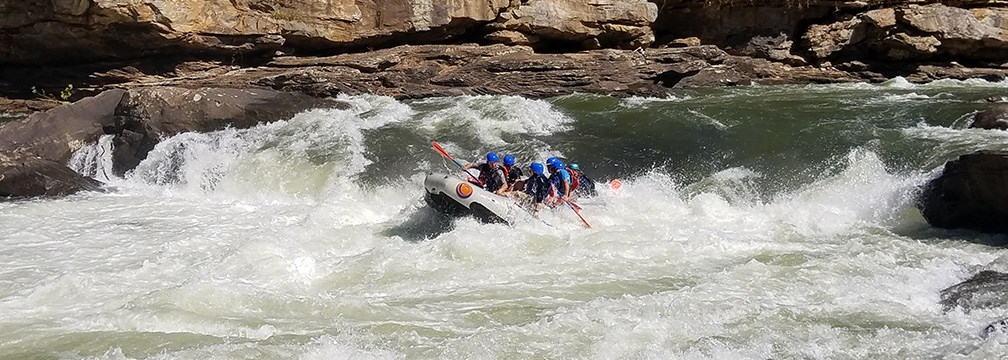 rafters paddle through big whitewater
