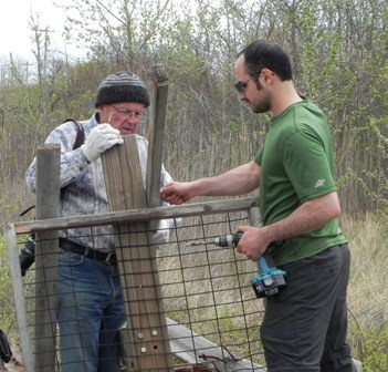 Volunteers Don Riepe and Shervin Hess build an osprey platform out of wood salvaged at the salt marsh.