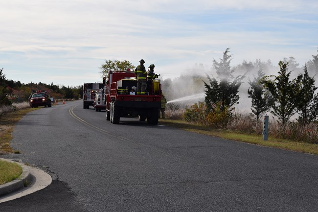 Photo showing various fire trucks hosing down trees in an interagency fire drill.