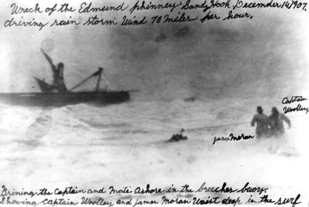 """Wreck of the Edmund J. Phinney Sandy Hook December 14, 1907. driving rain storm wind 70 miles per hour. Brin[g]ing the Captain and Mate ashore in the breeches buoy. Showing [USLSS] Captain Woolley and [USLSS] James Moran waist deep in the surf"""