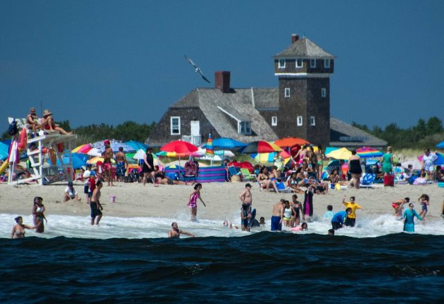Visitors enjoy the beach on a summer day, with the former U.S. Life Saving Station in the background.  Photo by Volunteer-in-Parks Stan Kosinski.