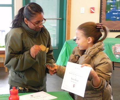 Park Guide Shalini Gopie awards a Junior Ranger badge during Junior Rangerpalooza at Great Kills Park.