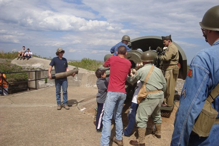 The public helps volunteers from Army Ground Forces Association to load the six inch gun at Battery Gunnison