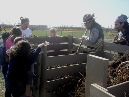 A Gateway park ranger helps students in RAA's after-school program learn how to compost garbage. Photo courtesy of RAA.