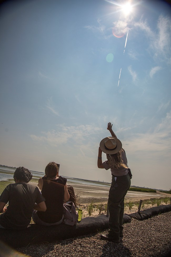 Ranger Erin Schoppmeyer points at the sun during the 2017 solar eclipse at the Jamaica Bay Wildlife Refuge