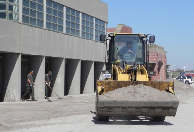 Maintenance employees at Gateway shovel sand at Jacob Riis Park, getting the park safe to reopen.