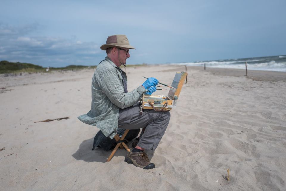 Photo of artist Christopher Wright painting at Fort TIlden