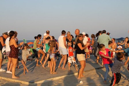 Concert goers having fun and dancing on the beach.