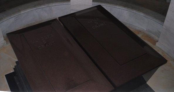 Two red granite sarcophagi sit side by side.